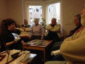 Charlie shows the group some photos and artefacts from the collection